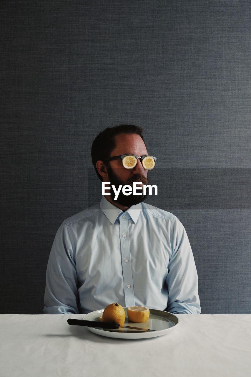 Man Wearing Eyeglasses Sitting At Table Against Gray Wall