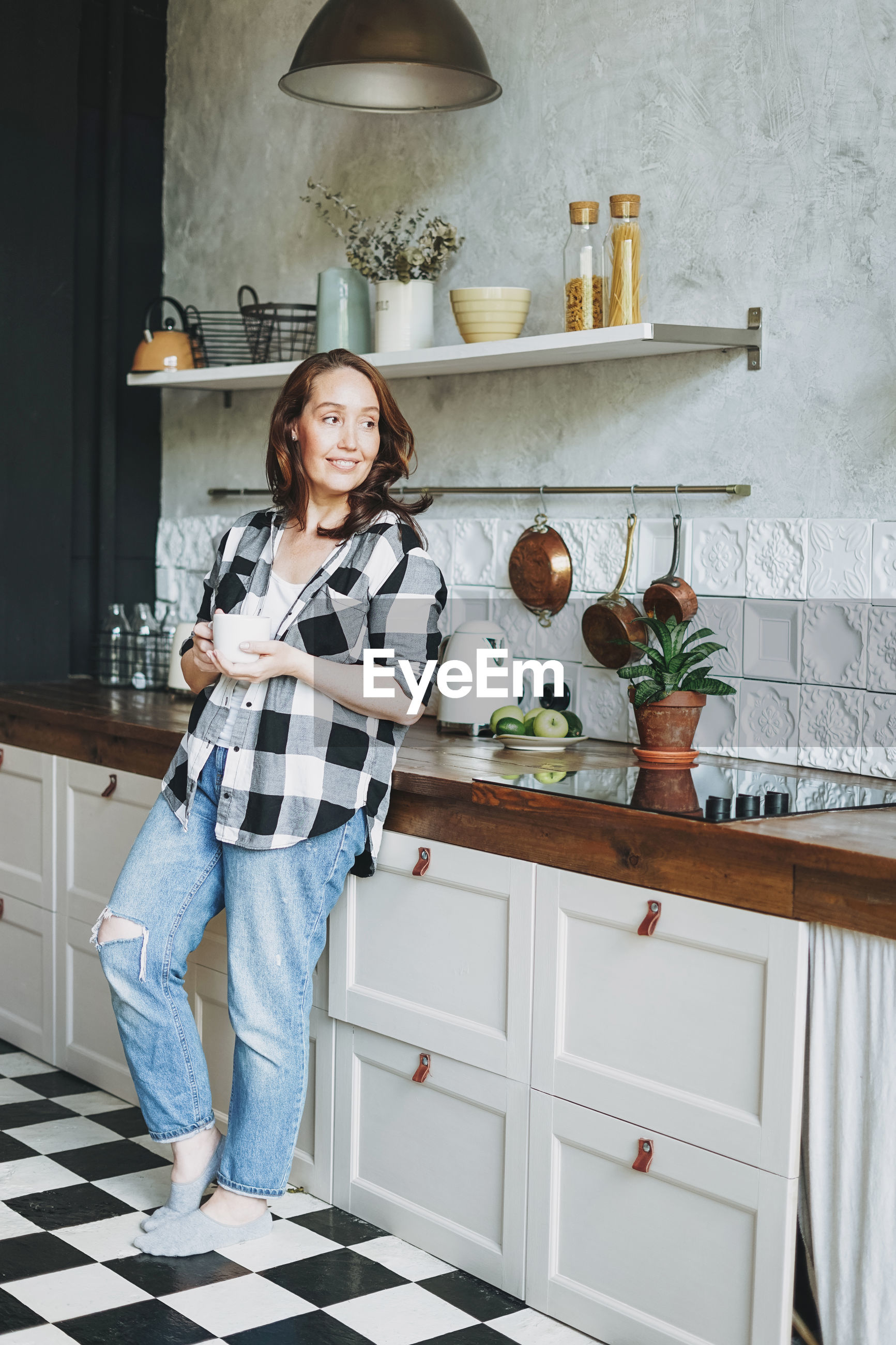 Smiling woman looking away while standing in kitchen