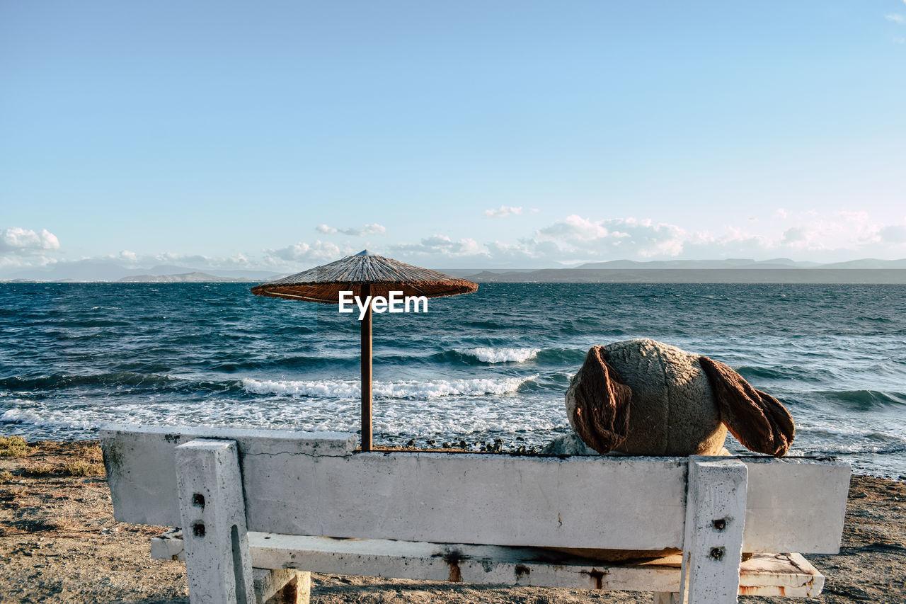 Teddy Bear On Bench At Beach Against Blue Sky During Sunny Day