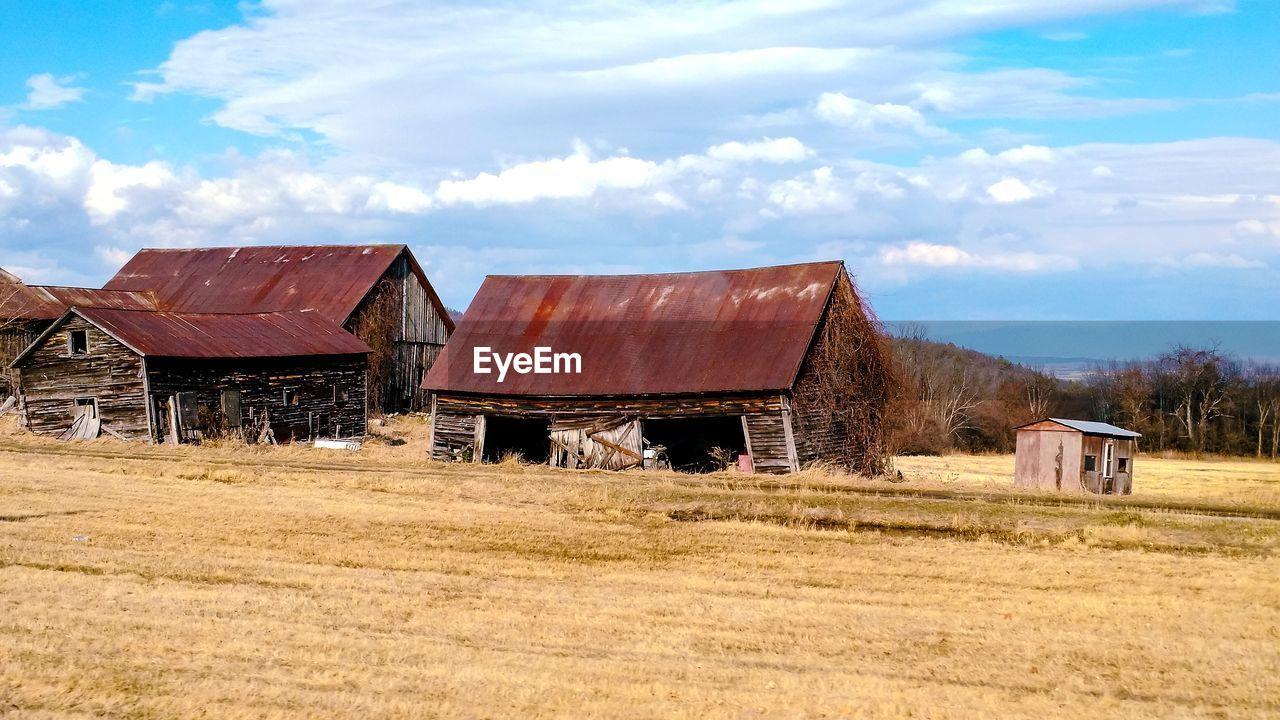 Abandoned farm buildings in field against sky