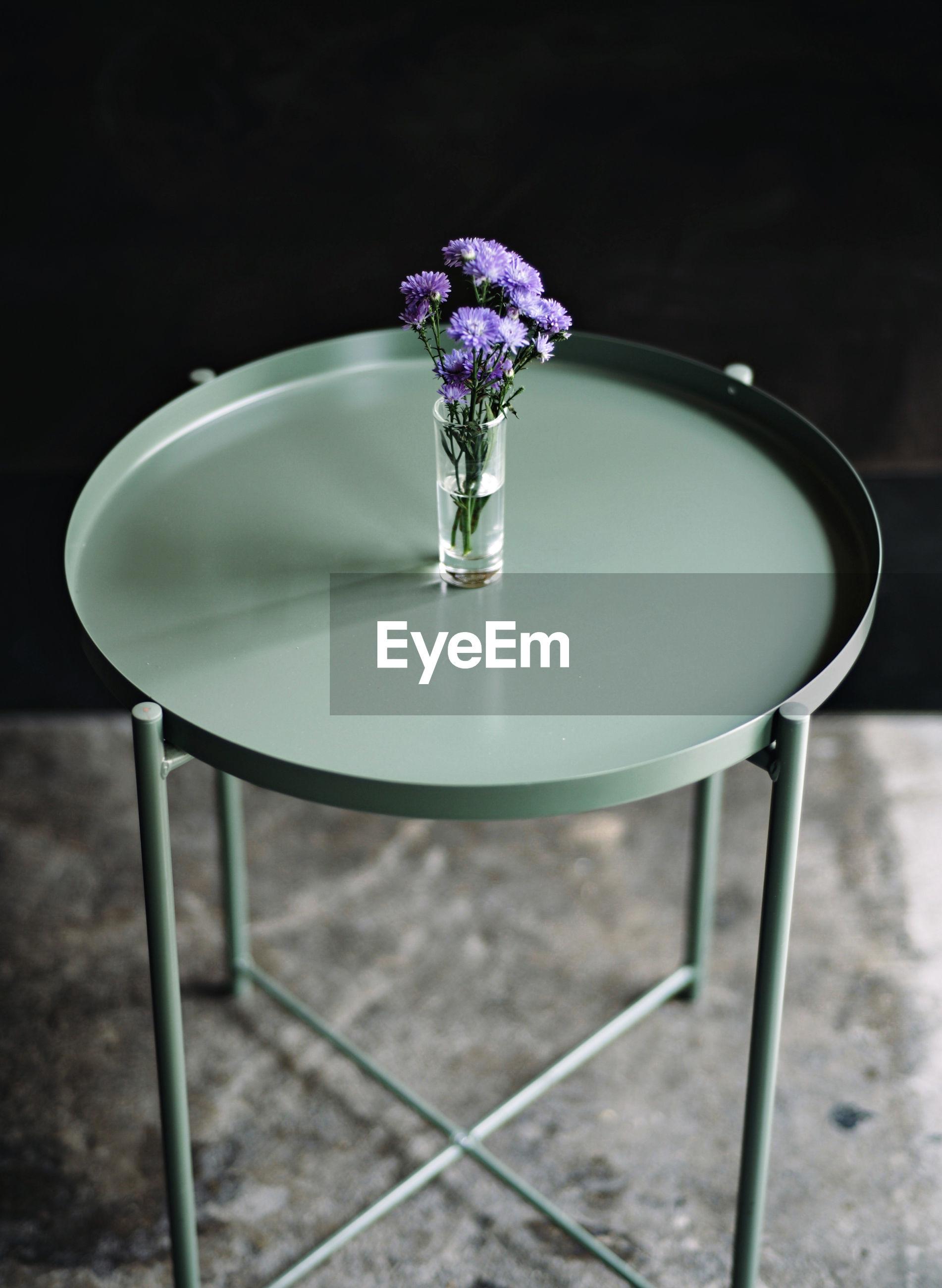 PURPLE FLOWER VASE ON TABLE AGAINST WALL