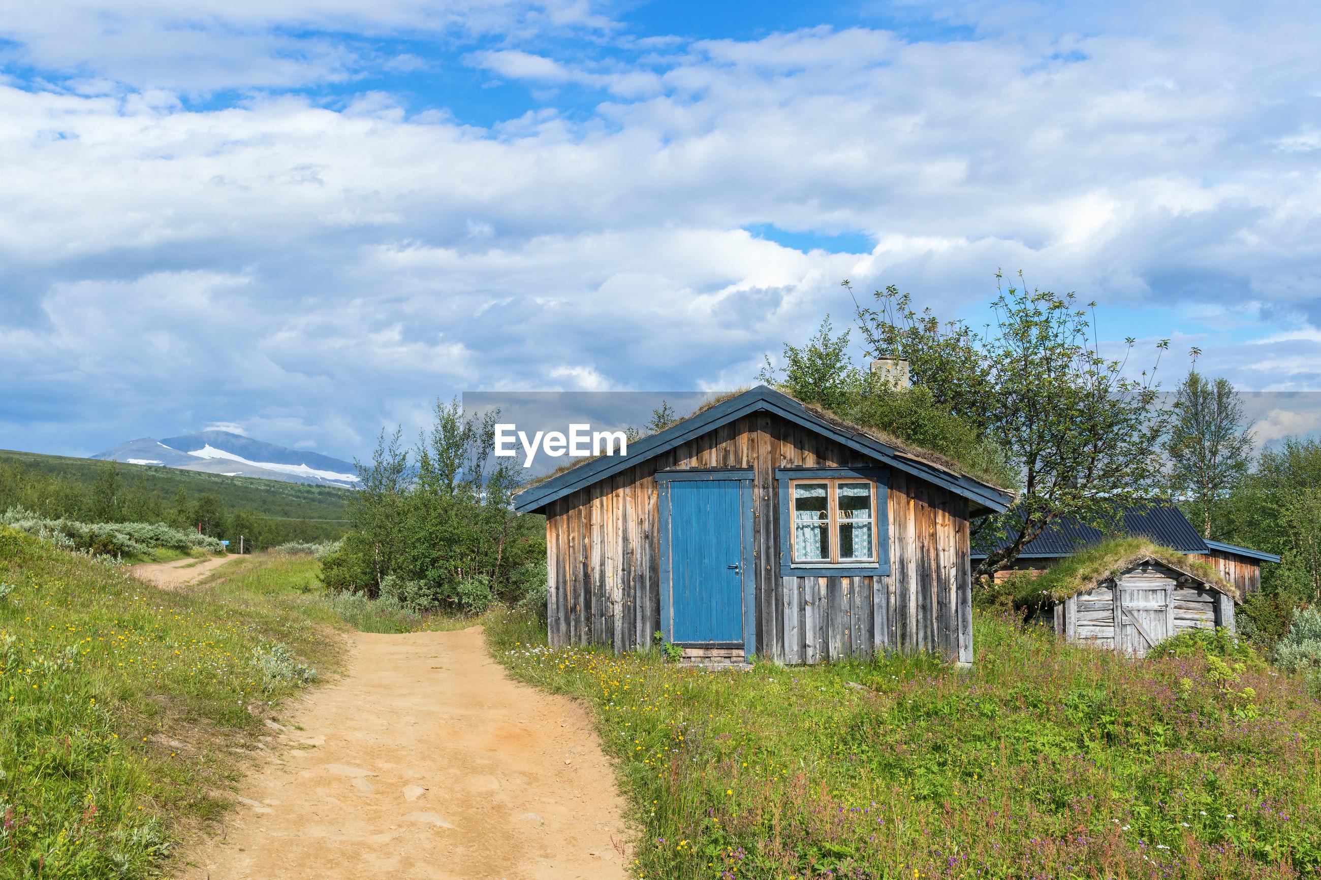 HOUSE ON GRASS AGAINST SKY