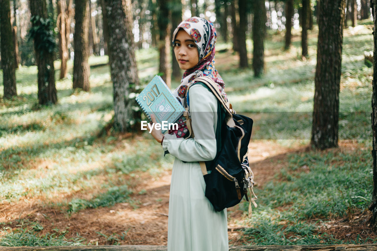 tree, forest, one person, lifestyles, leisure activity, young adult, headwear, standing, nature, young women, real people, outdoors, day, portrait, people, adult