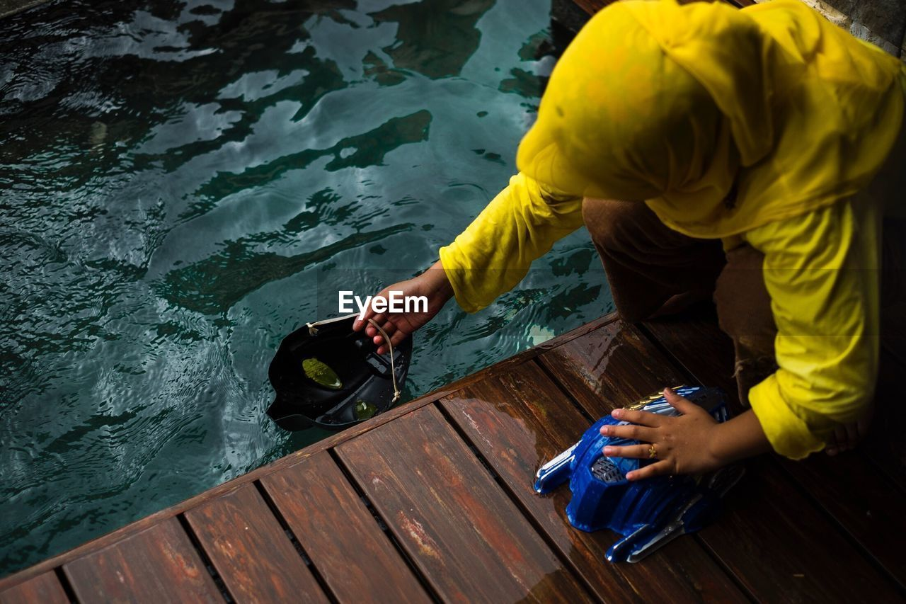 High Angle View Of Child Filling Water In Mask On Pier Over Lake