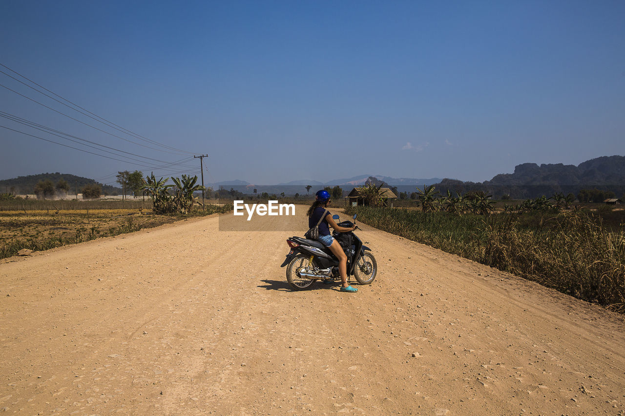 Woman Riding Motorcycle On Dirt Road Against Sky