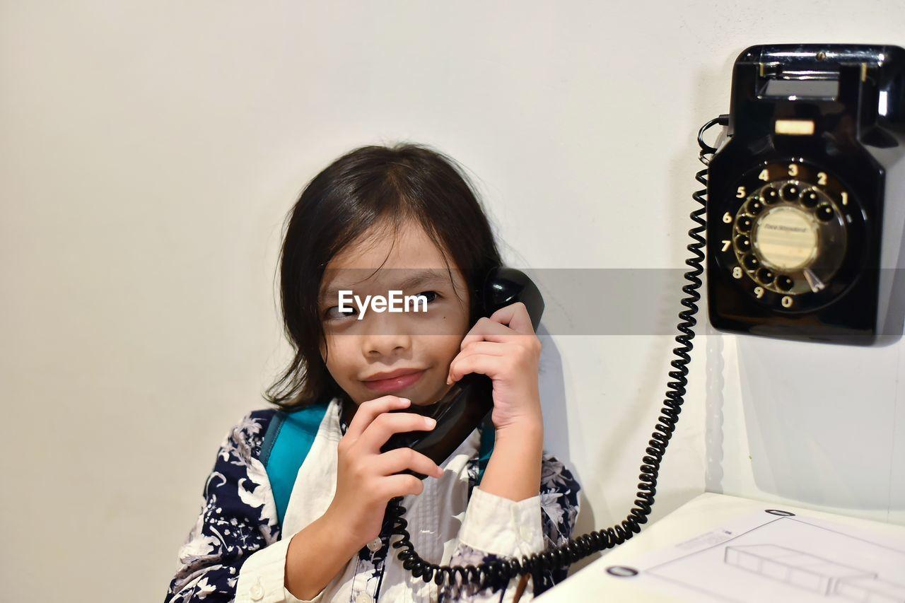 Cute girl talking on telephone in home