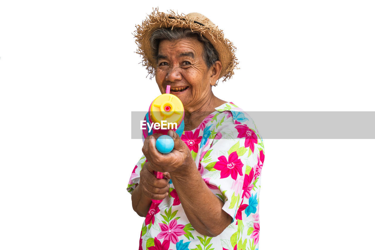 Portrait of senior woman with squirt gun standing against white background