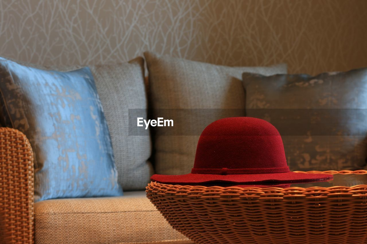 Close-up of hat on sofa against wall at home