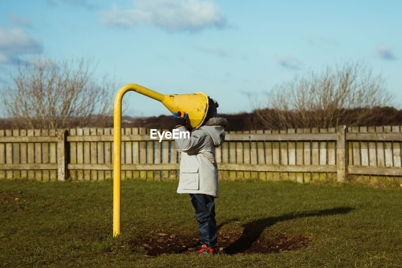 one person, sky, nature, full length, plant, day, real people, field, fence, barrier, boundary, yellow, land, holding, lifestyles, standing, tree, protection, leisure activity, obscured face