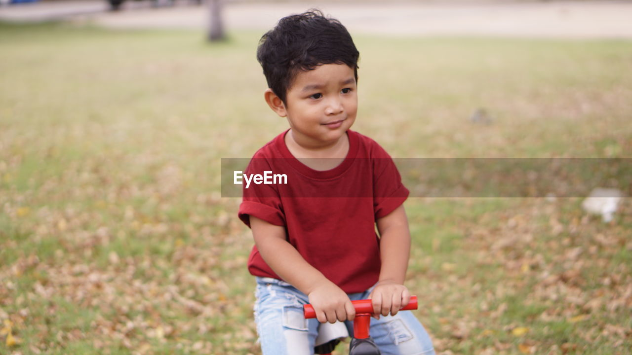 child, childhood, boys, one person, men, males, field, casual clothing, land, front view, leisure activity, three quarter length, focus on foreground, day, lifestyles, real people, looking, nature, outdoors, innocence, shorts