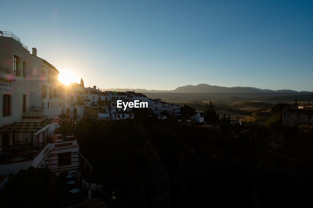 Spainish town against clear sky during sunrise