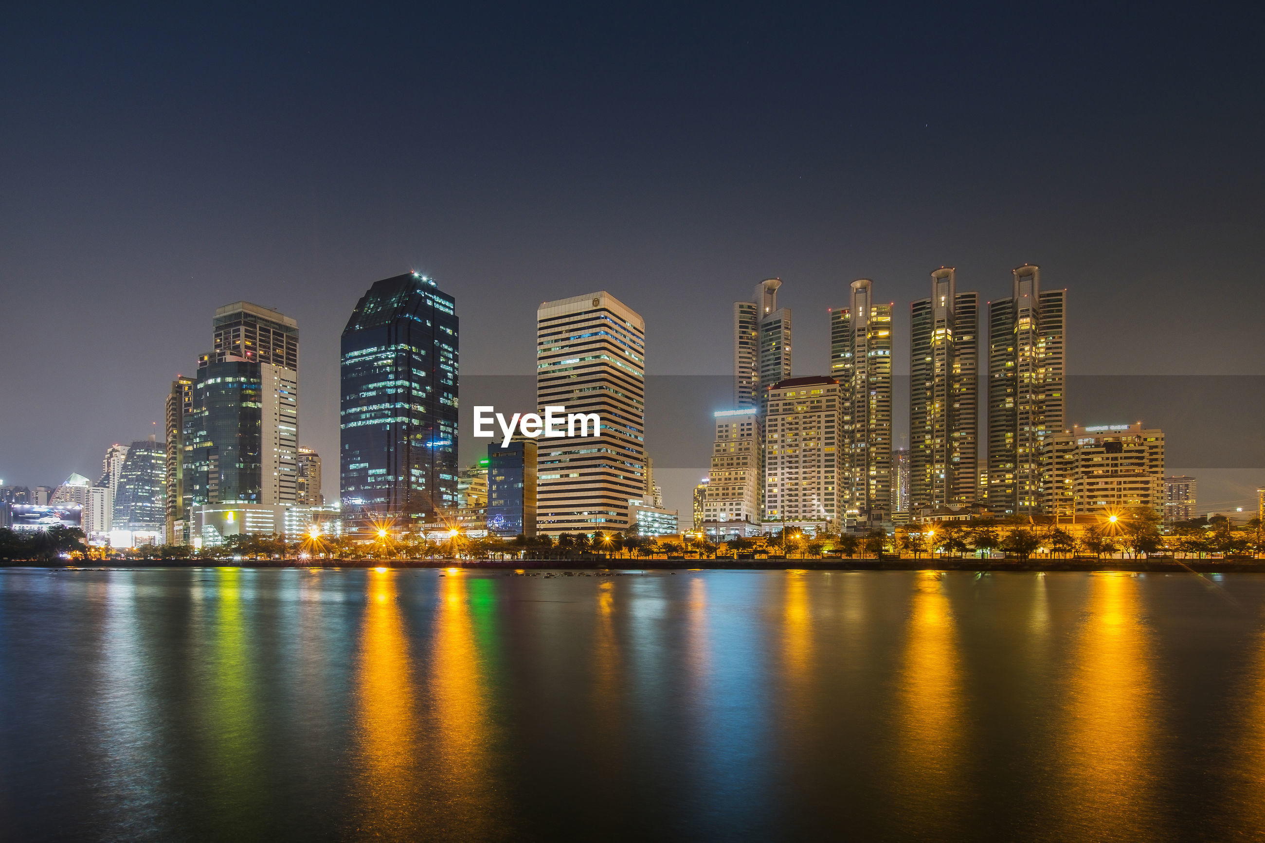 ILLUMINATED MODERN BUILDINGS BY BAY AGAINST SKY