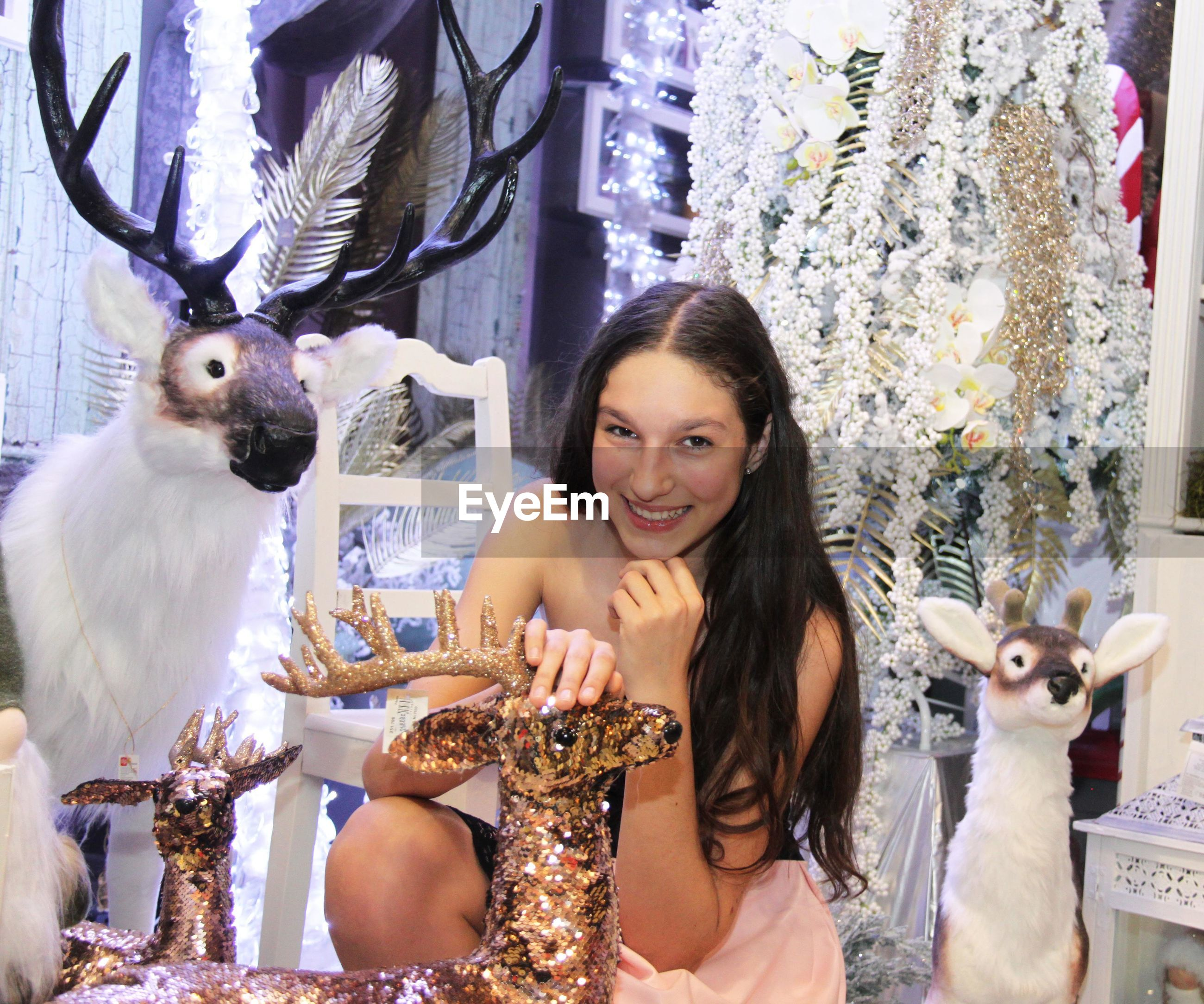 Portrait of smiling teenage girl crouching by christmas decorations in store
