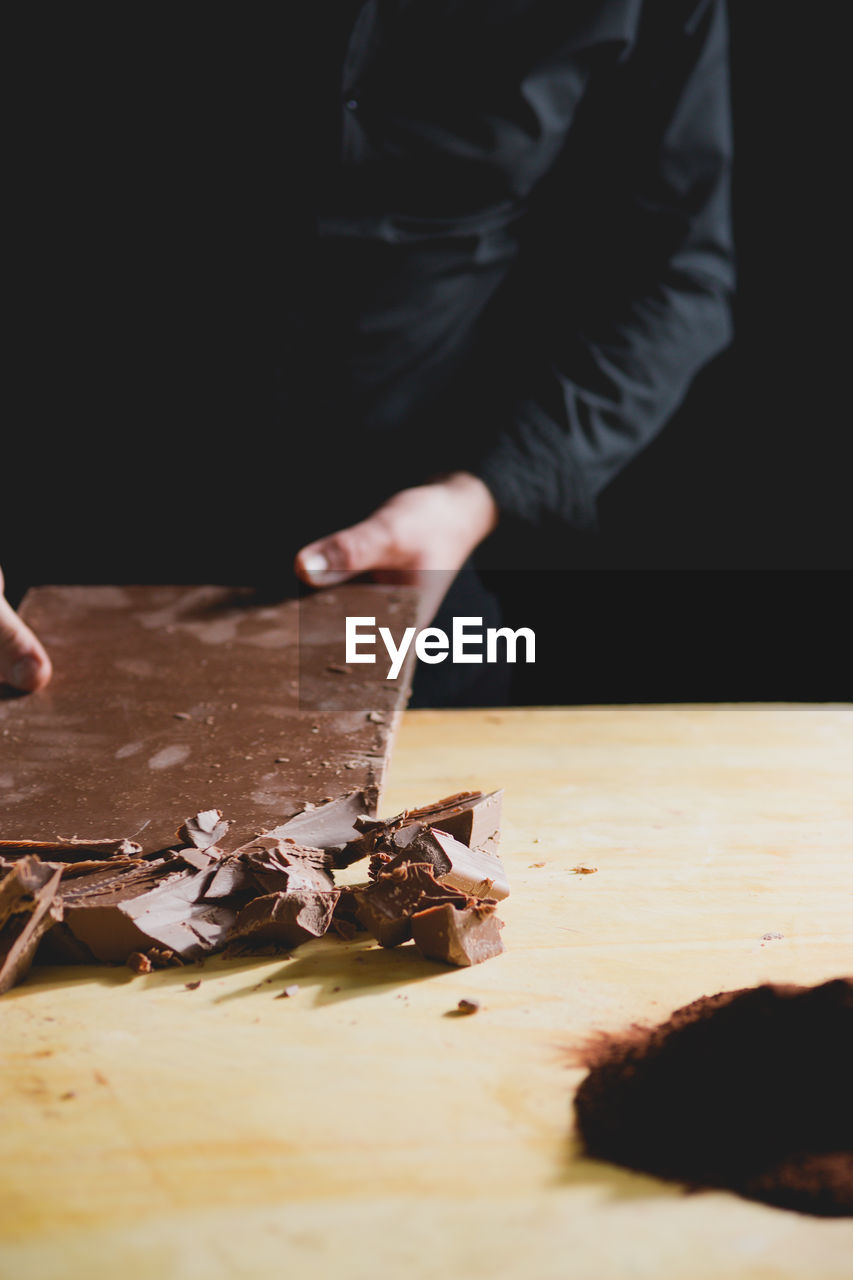 Midsection Of Man Breaking Chocolate