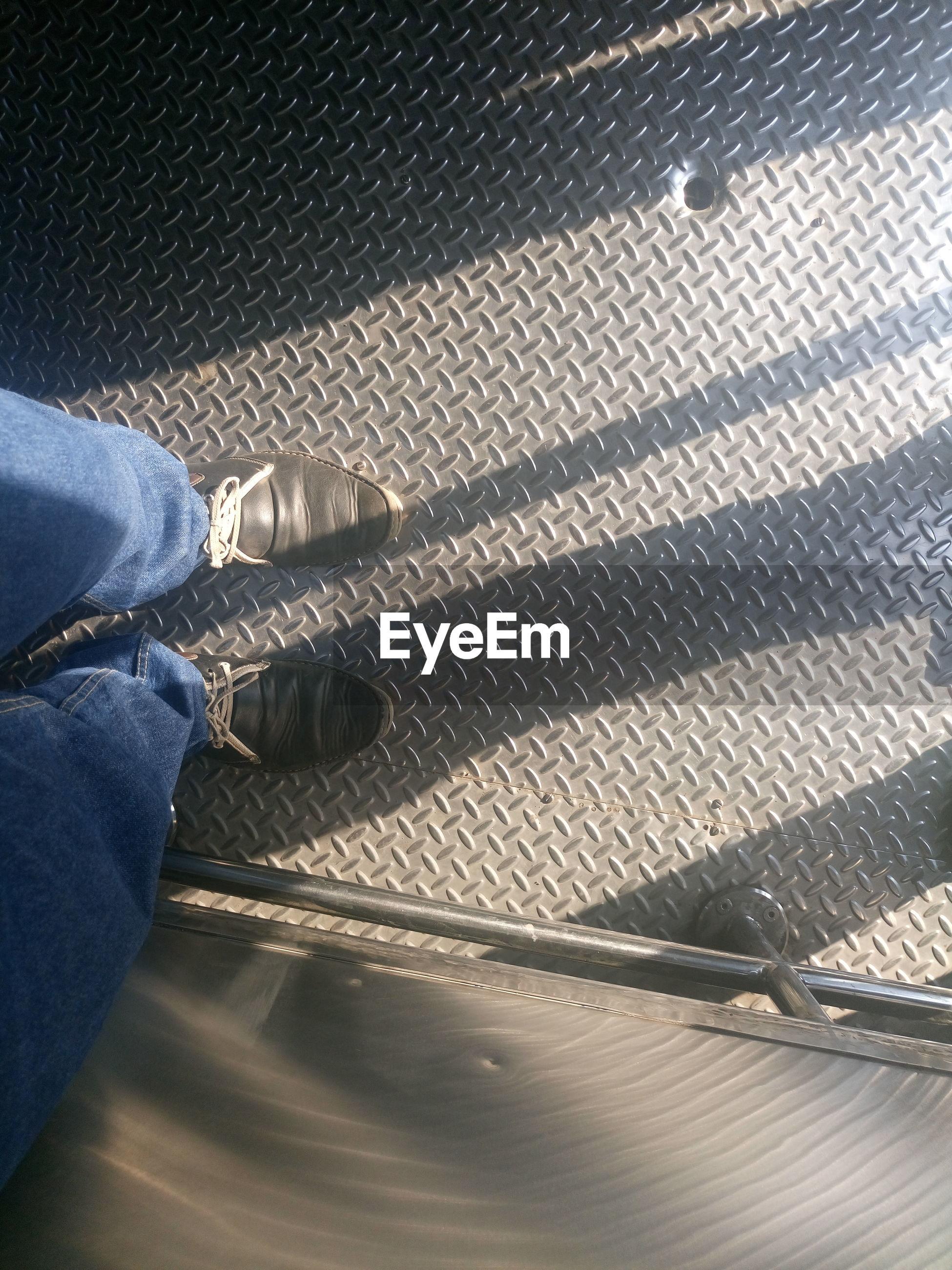 Low section of man standing on metal floor in train