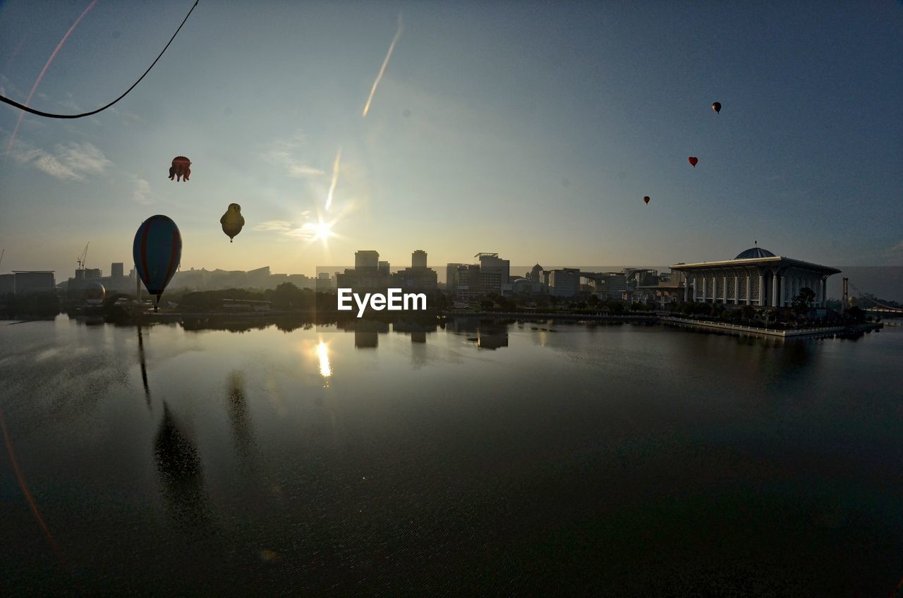 sun, sunset, sunbeam, architecture, reflection, building exterior, sky, built structure, sunlight, water, mid-air, outdoors, city, no people, nature, flying, day, hot air balloon, cityscape