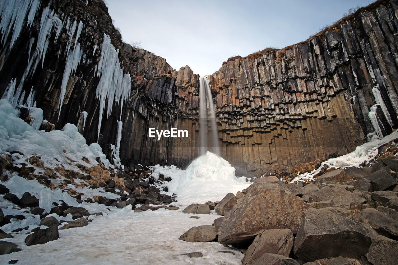 Low Angle View Of Icicles And Waterfall During Winter