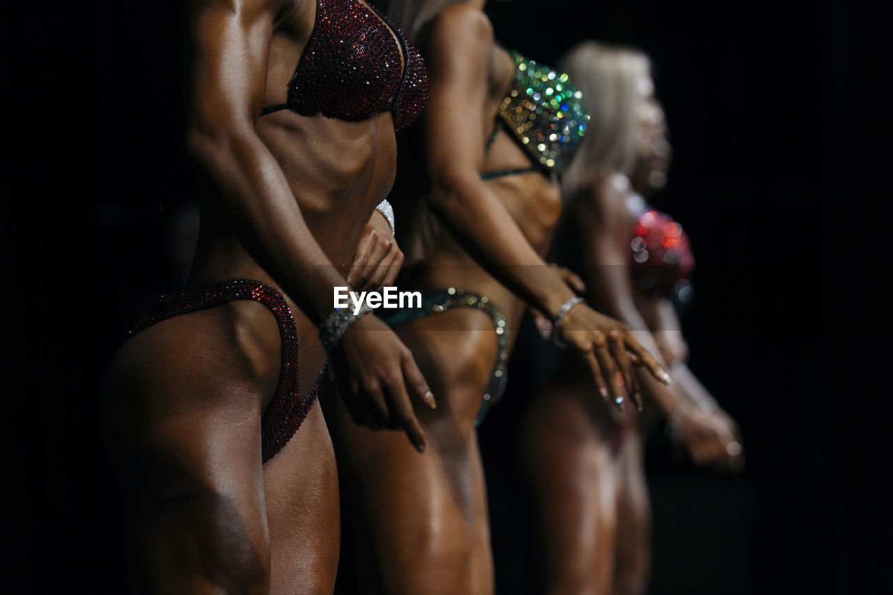 Midsection Of Female Athletes Posing Against Black Background