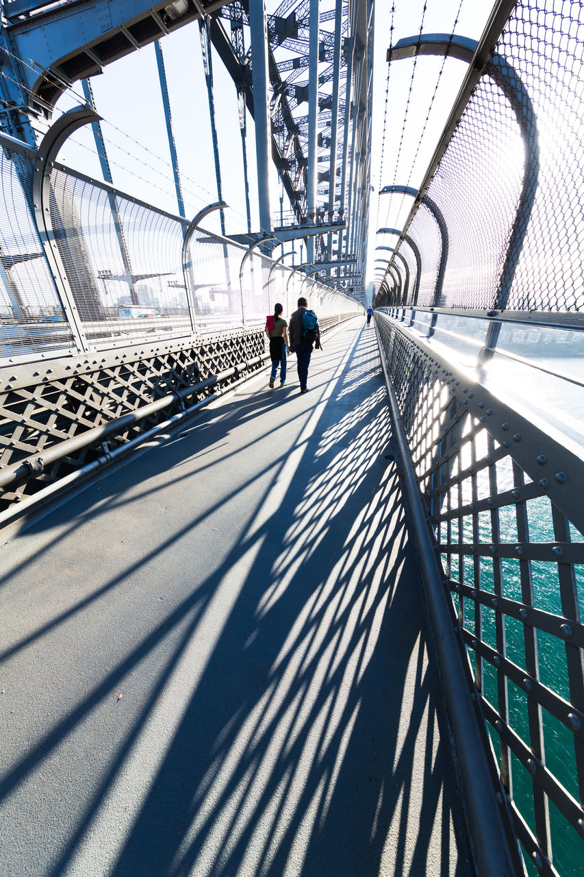 real people, architecture, built structure, men, shadow, transportation, sunlight, day, railing, lifestyles, walking, group of people, nature, bridge, adult, women, people, full length, bridge - man made structure, outdoors, footbridge