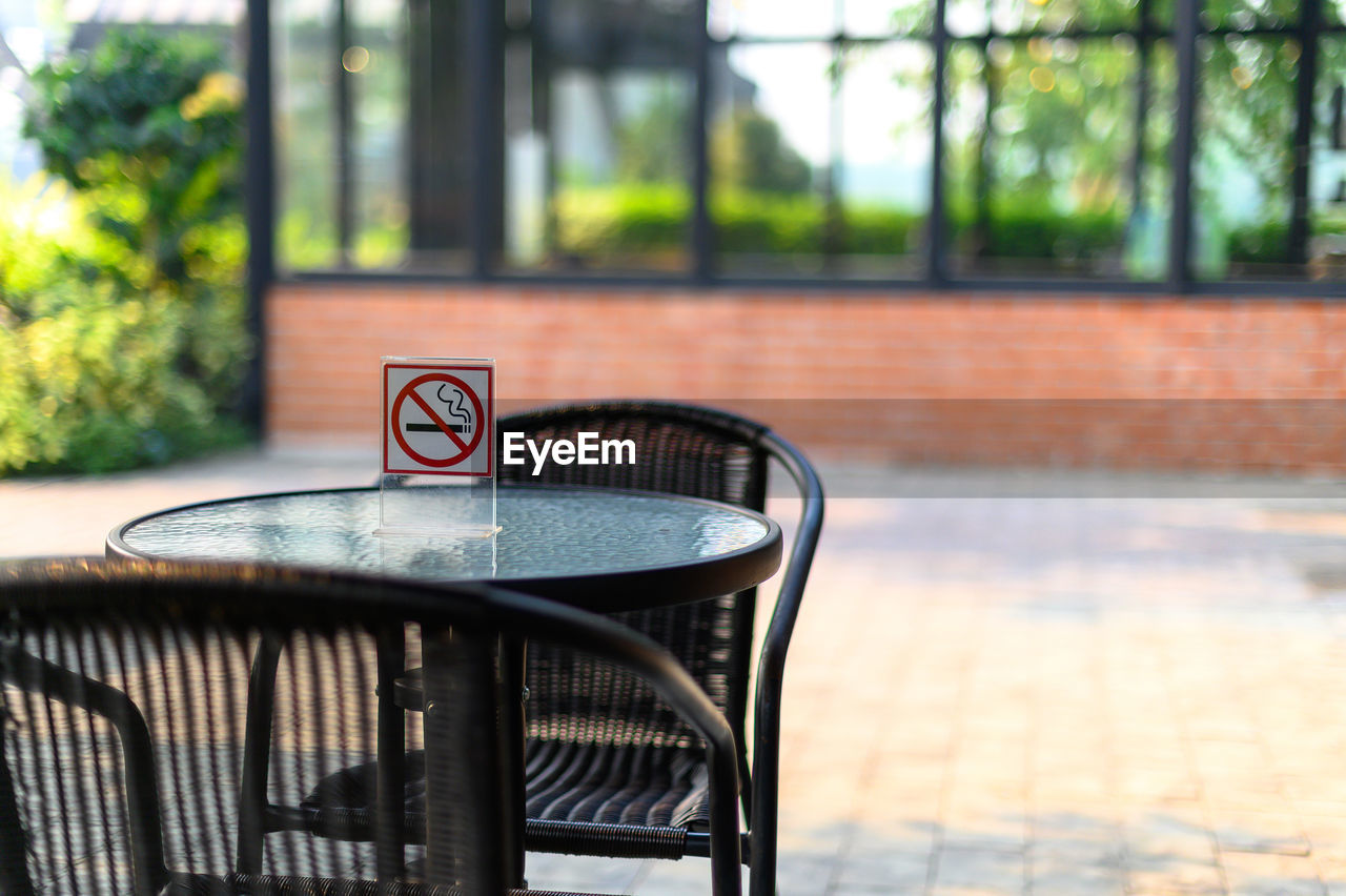 focus on foreground, table, day, no people, seat, chair, absence, outdoors, food and drink, close-up, architecture, railing, metal, restaurant, built structure, nature, window, communication, glass - material, plant
