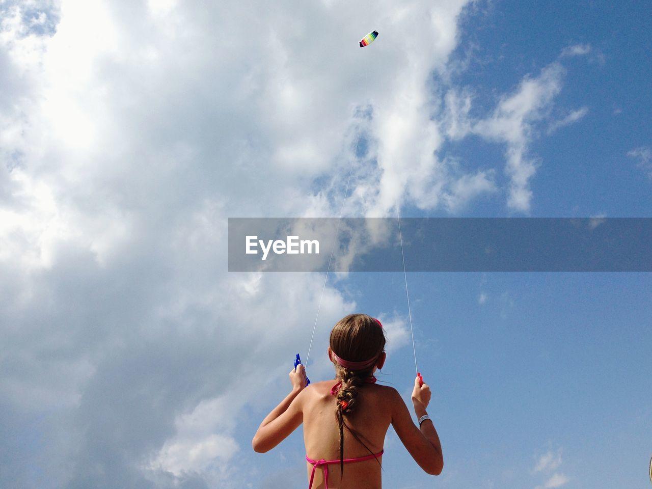 Rear view of girl flying kite against sky