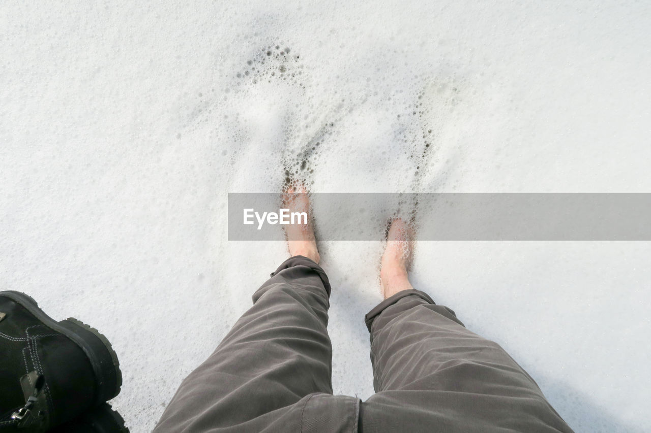 low section, one person, human body part, body part, human leg, real people, personal perspective, lifestyles, men, standing, leisure activity, sport, water, nature, day, aquatic sport, land, shoe, outdoors, human foot