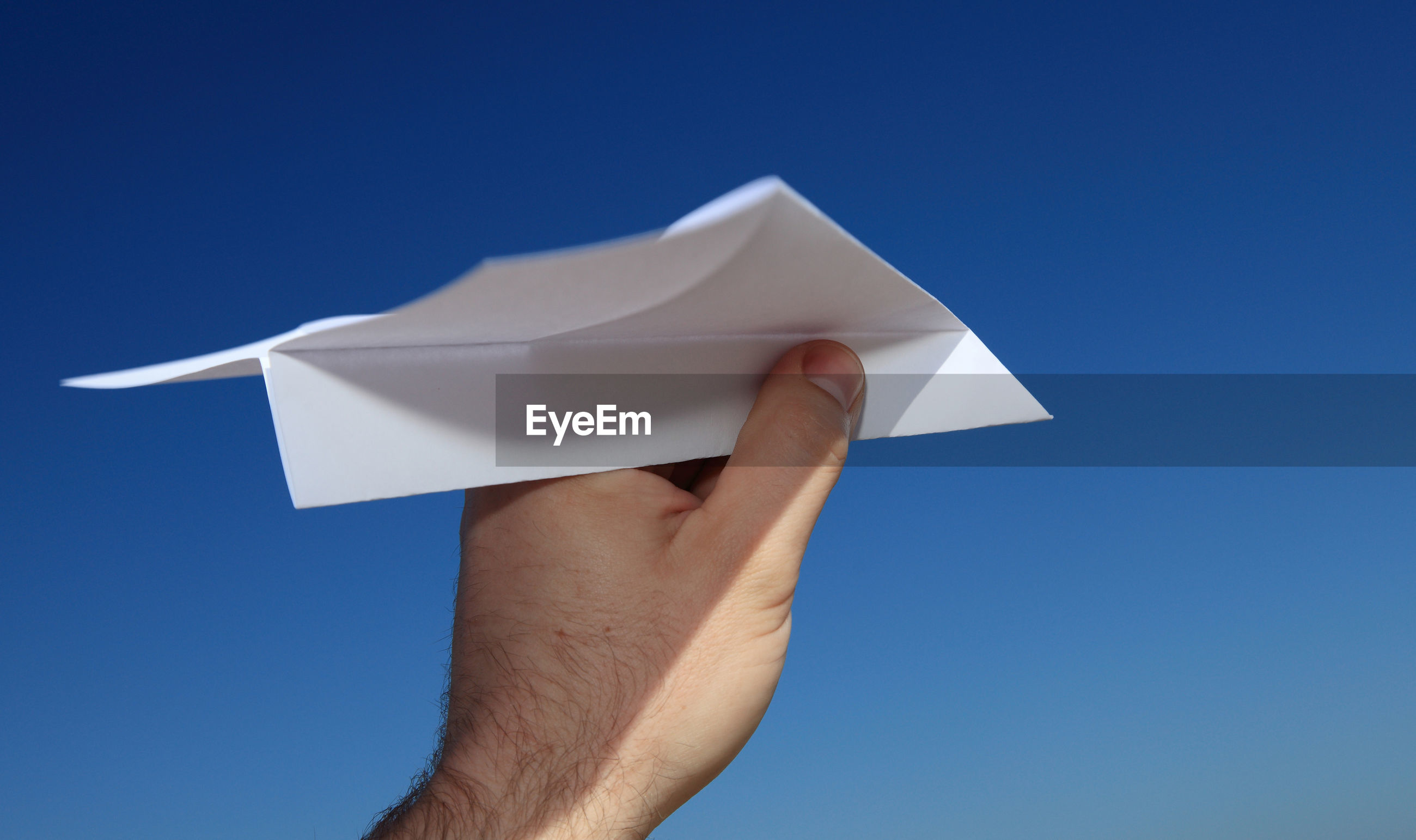 Cropped hand of paper airplane against clear blue sky