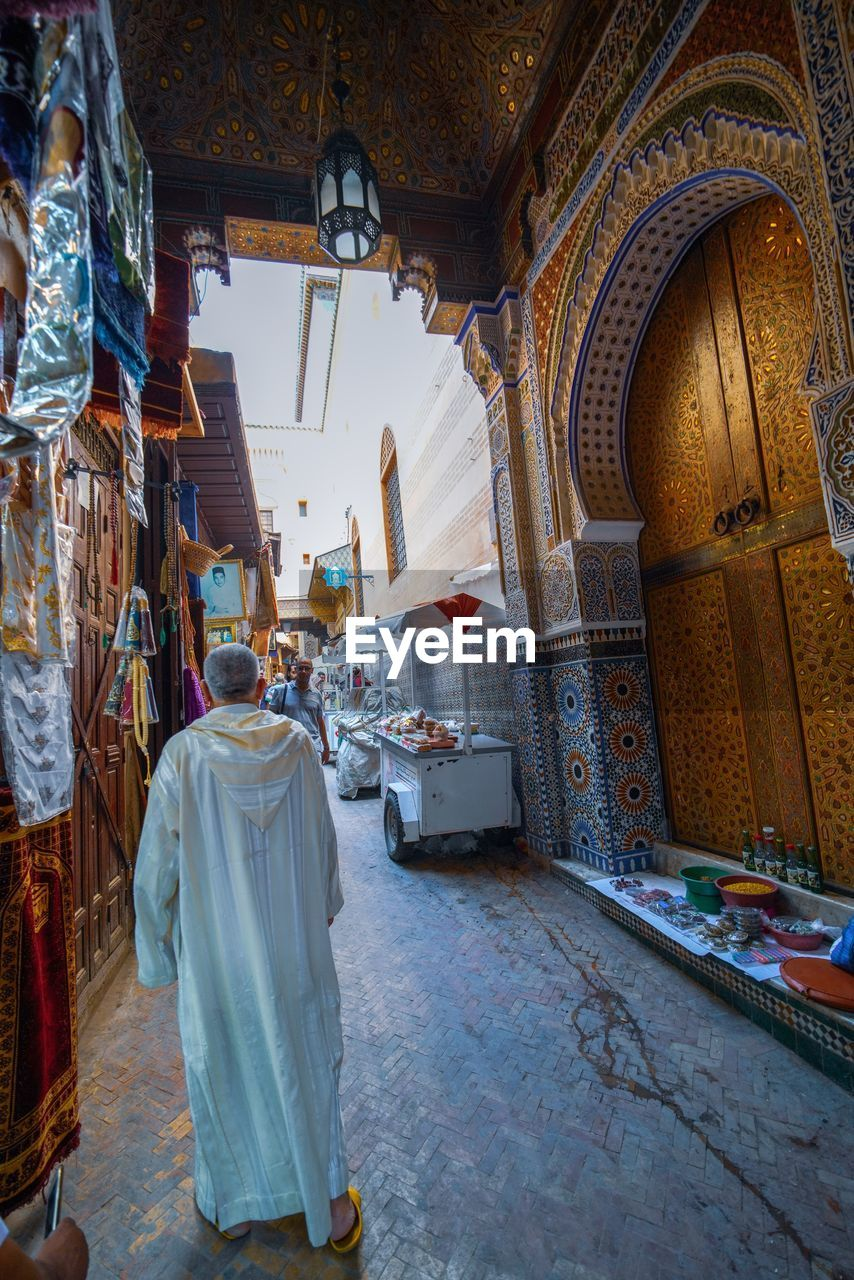 religion, belief, architecture, indoors, built structure, spirituality, place of worship, rear view, building, full length, day, one person, real people, women, adult, clothing, lifestyles