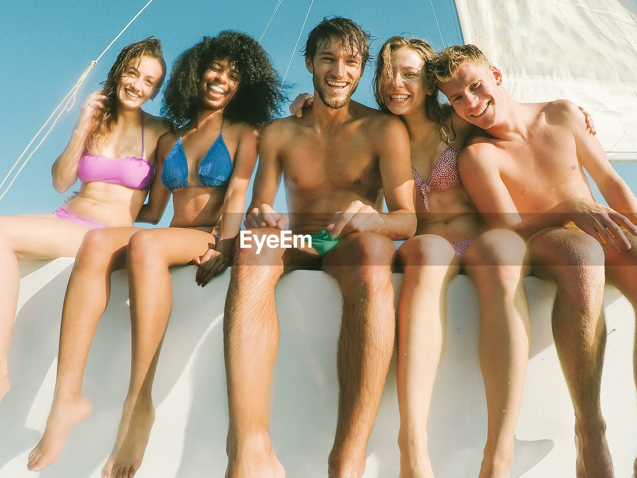 Low Angle Portrait Of Cheerful Friends Sitting On Boat
