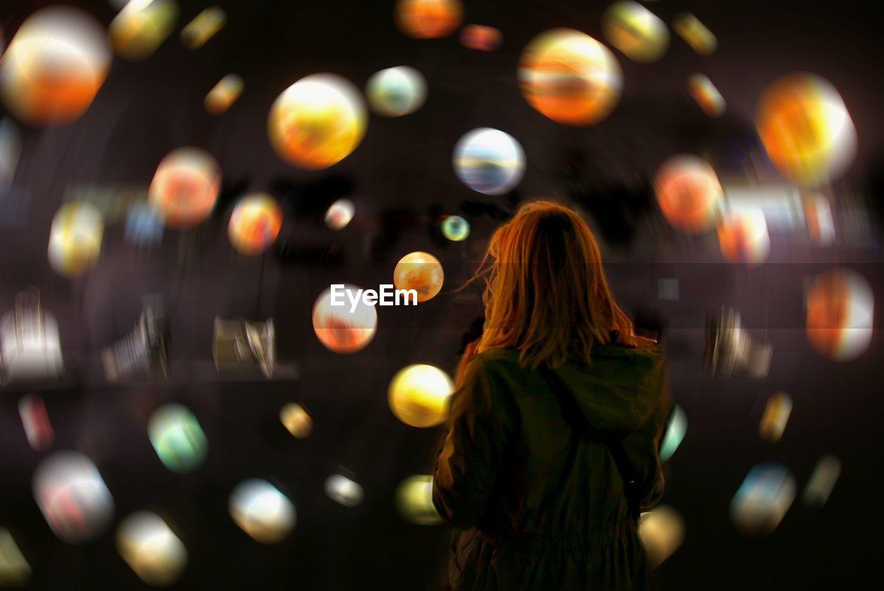 Rear View Of Woman Standing Against Defocused Spheres