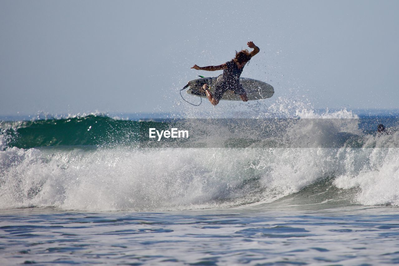 motion, water, sea, sport, splashing, real people, leisure activity, waterfront, lifestyles, aquatic sport, one person, wave, extreme sports, skill, adventure, surfing, nature, enjoyment, outdoors, power in nature