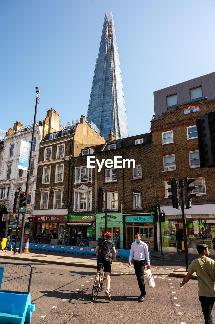 REAR VIEW OF PEOPLE ON STREET AGAINST BUILDINGS