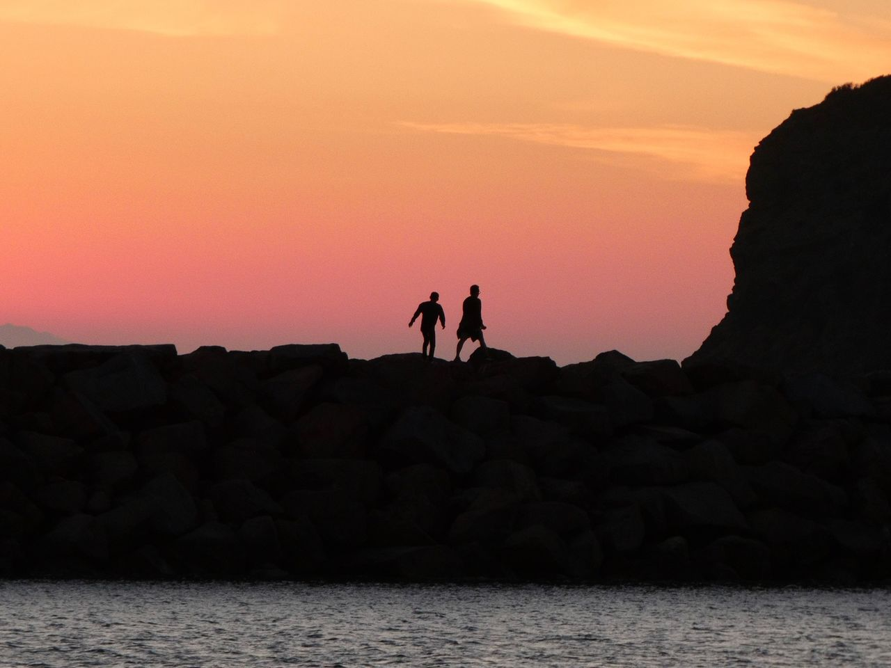 Silhouette People On Rock By Sea Against Sky During Sunset