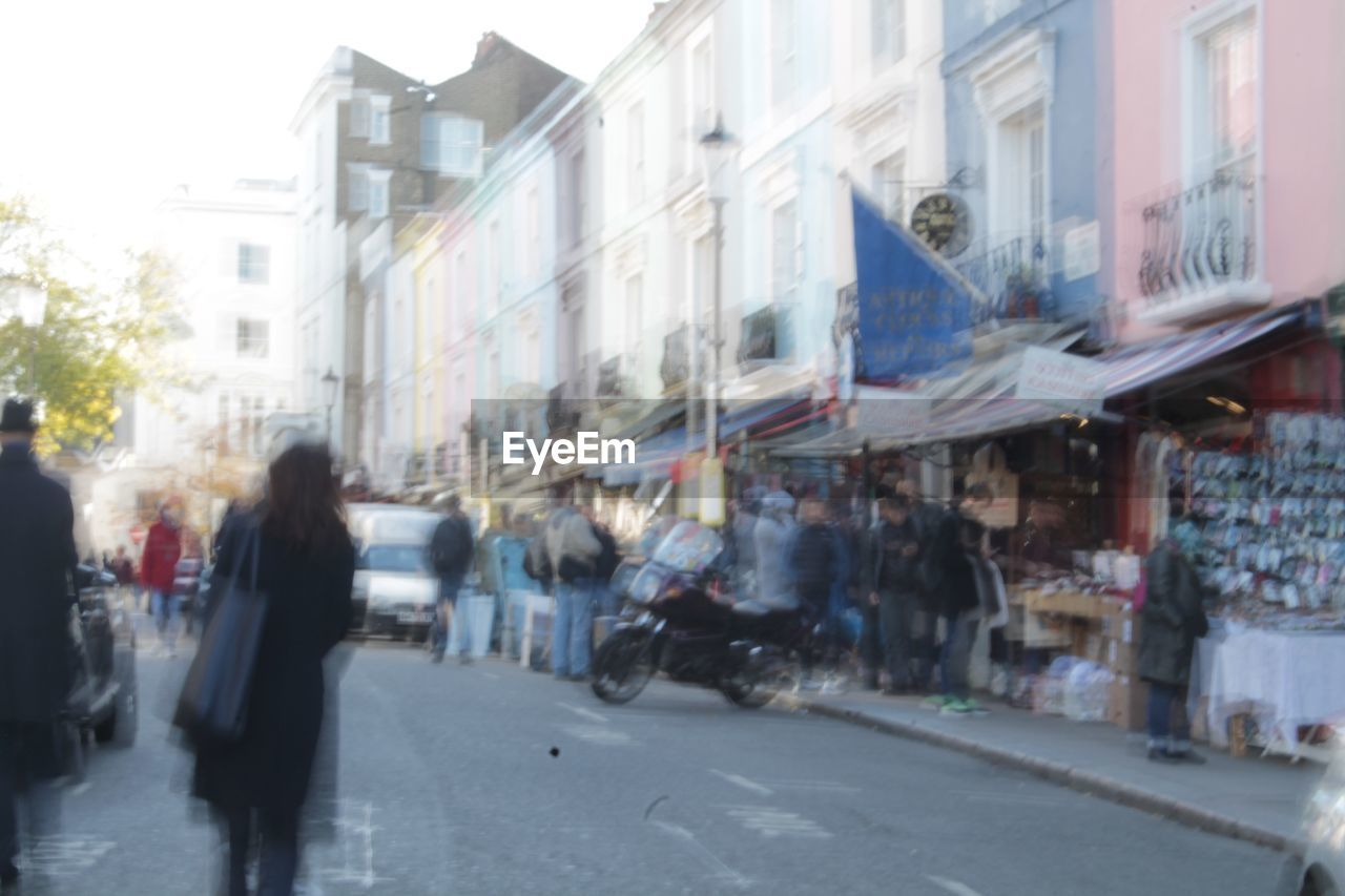 city, architecture, building exterior, built structure, street, walking, city life, group of people, transportation, real people, blurred motion, day, incidental people, motion, men, road, women, outdoors, people, city street