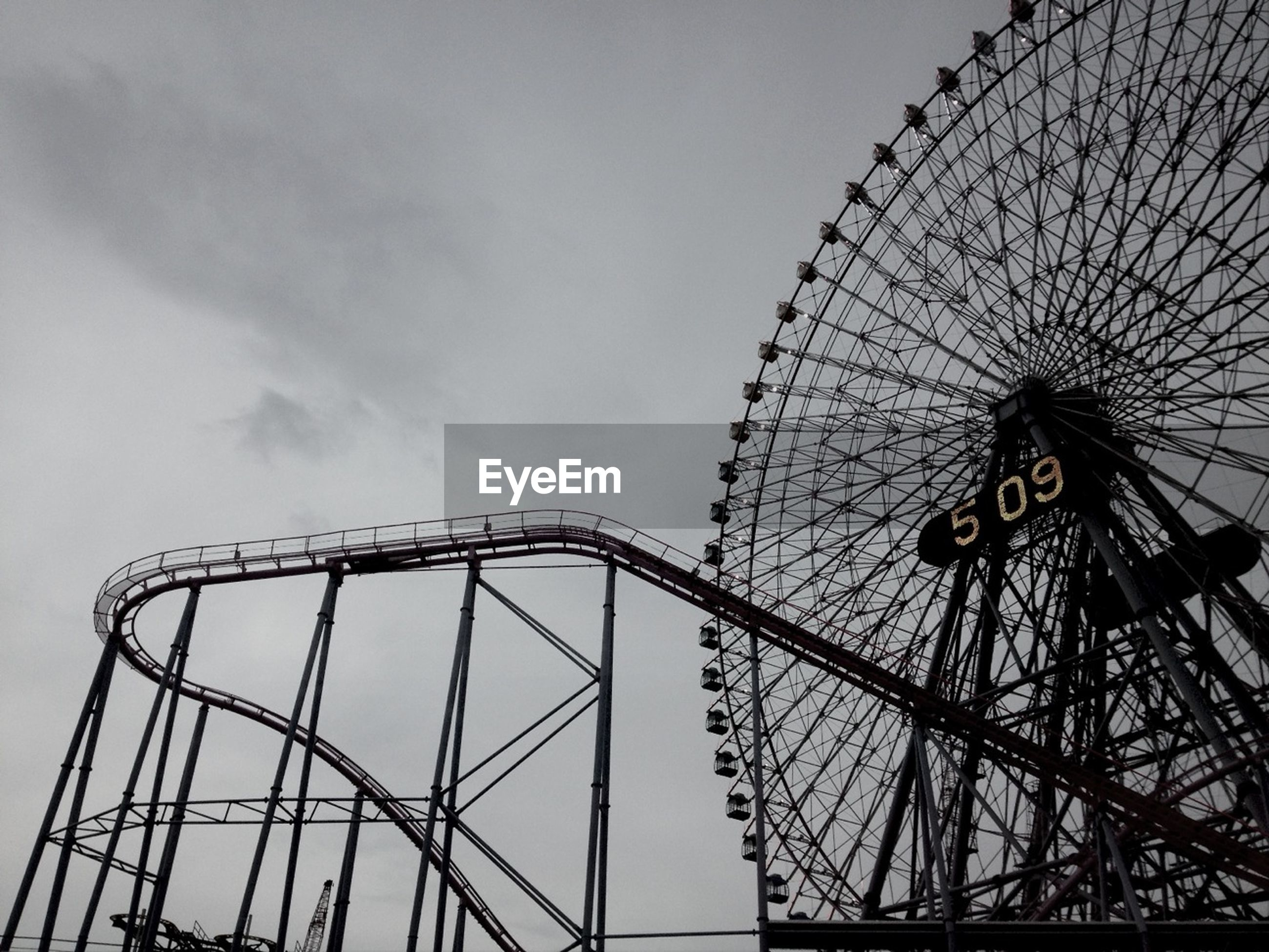 amusement park, ferris wheel, amusement park ride, low angle view, arts culture and entertainment, sky, metal, built structure, fairground, day, outdoors, big wheel, large, fun, cloud - sky, part of, no people, fairground ride, clear sky, metallic