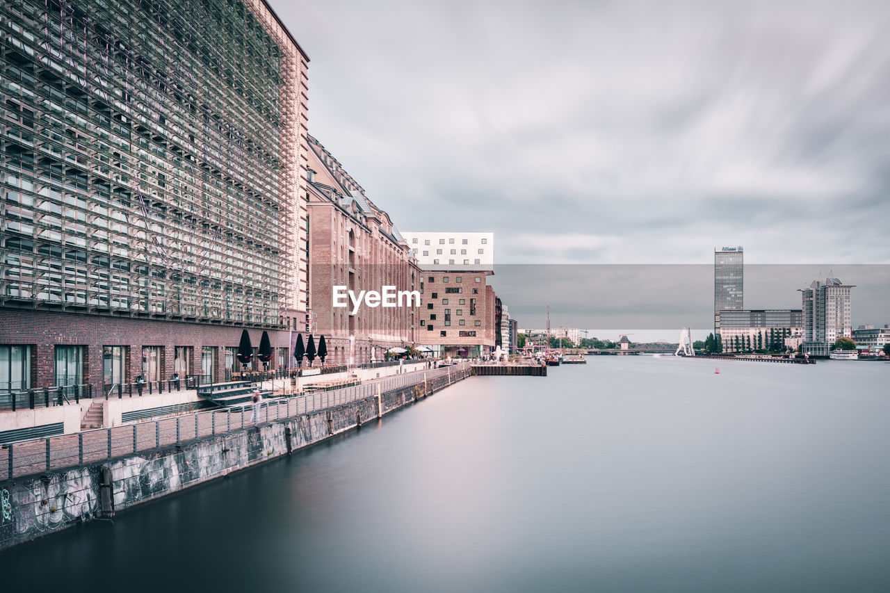 River By Buildings Against Cloudy Sky