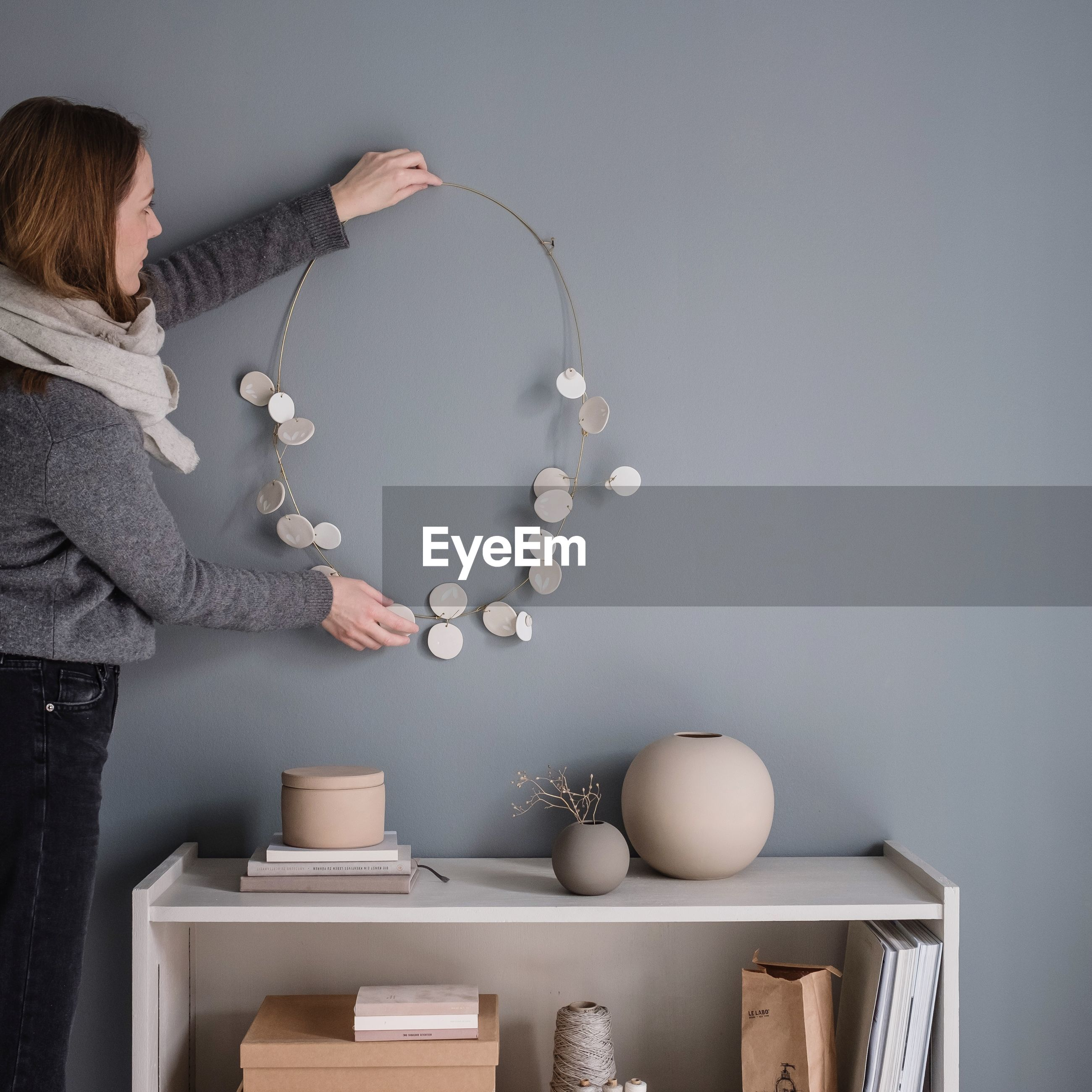 Woman hanging decoration on wall at home