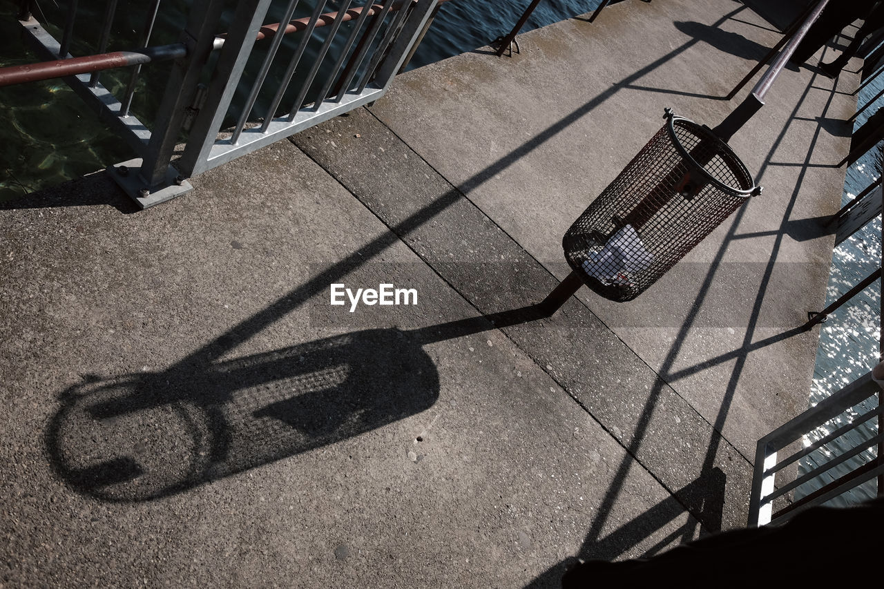 shadow, sunlight, high angle view, day, nature, no people, metal, outdoors, street, city, sunny, seat, chair, footpath, low section, bicycle, focus on shadow