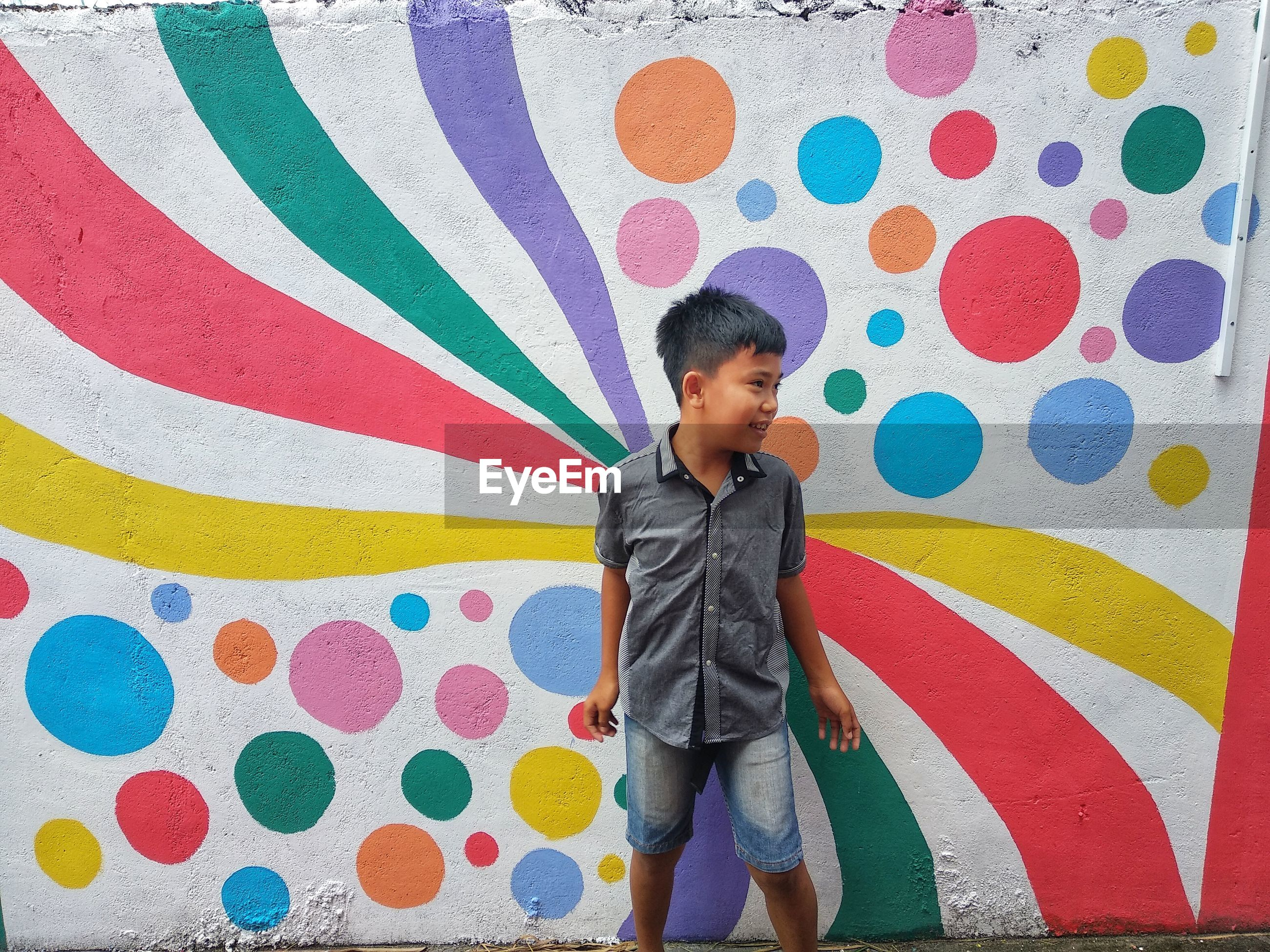 BOY STANDING ON MULTI COLORED WALL