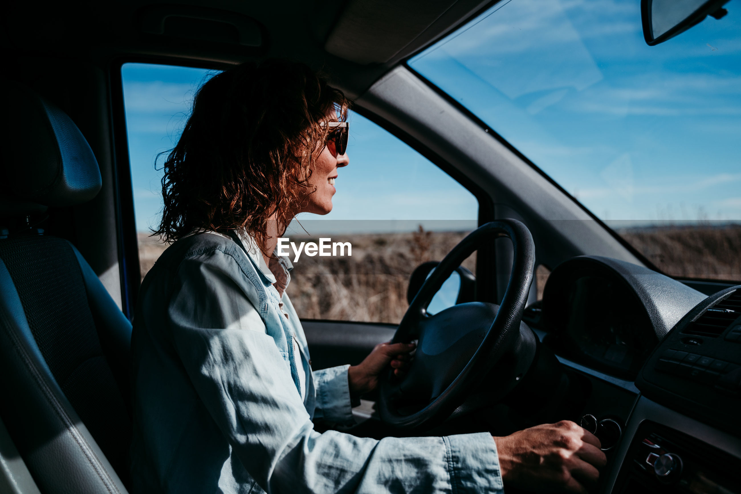 Side view of woman sitting driving car