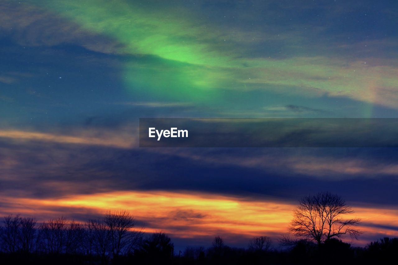 dramatic sky, sunset, silhouette, cloud - sky, scenics, sky, beauty in nature, nature, tree, atmospheric mood, orange color, tranquil scene, weather, majestic, multi colored, tranquility, no people, night, bare tree, outdoors, low angle view, illuminated, awe, star - space, astronomy, space, galaxy