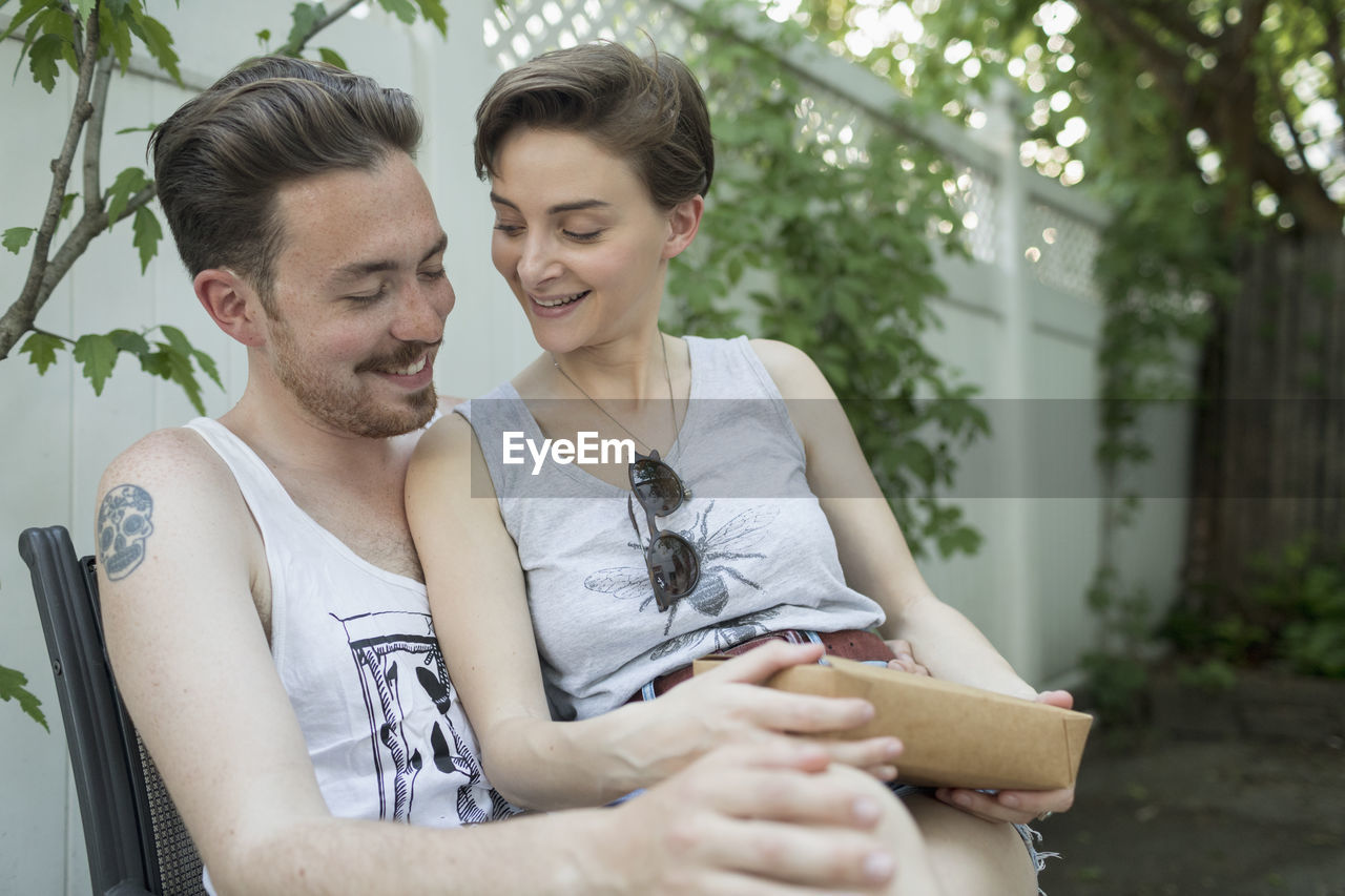 two people, togetherness, young adult, couple - relationship, emotion, young men, real people, young women, leisure activity, lifestyles, women, casual clothing, heterosexual couple, smiling, men, happiness, focus on foreground, bonding, sitting, positive emotion, outdoors