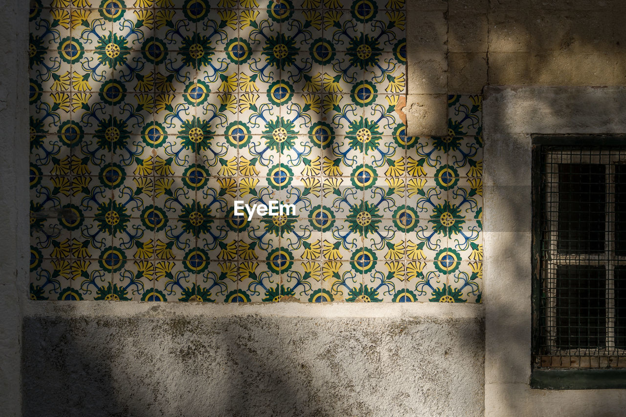 architecture, wall - building feature, pattern, tile, indoors, flooring, built structure, no people, design, day, building, window, art and craft, multi colored, mosaic, text, tiled floor, creativity, full frame, floral pattern, ornate