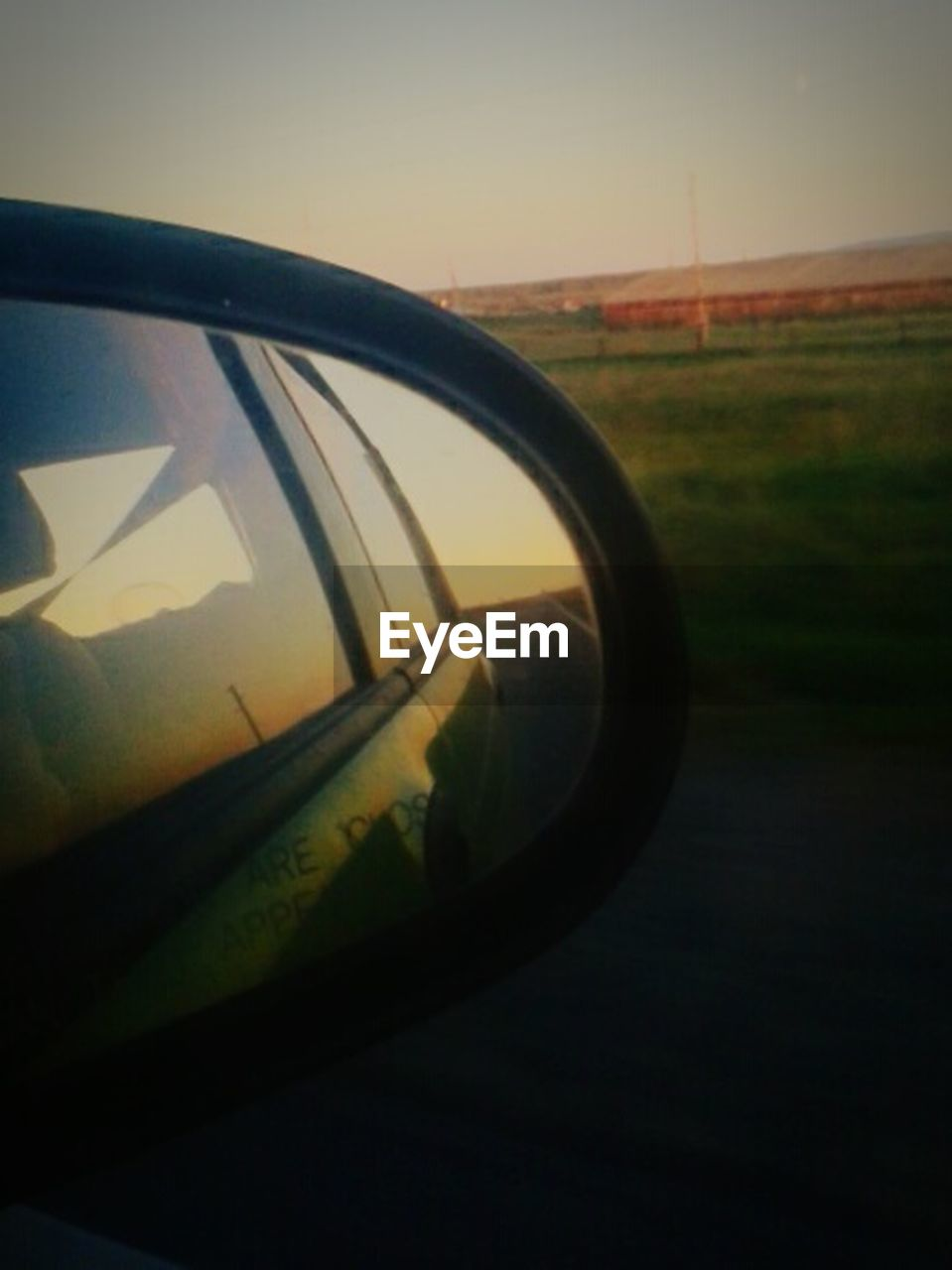 sky, transportation, mode of transportation, sunset, nature, no people, car, motor vehicle, reflection, land vehicle, glass - material, side-view mirror, grass, outdoors, close-up, travel, road, day, field, landscape, road trip, vehicle mirror