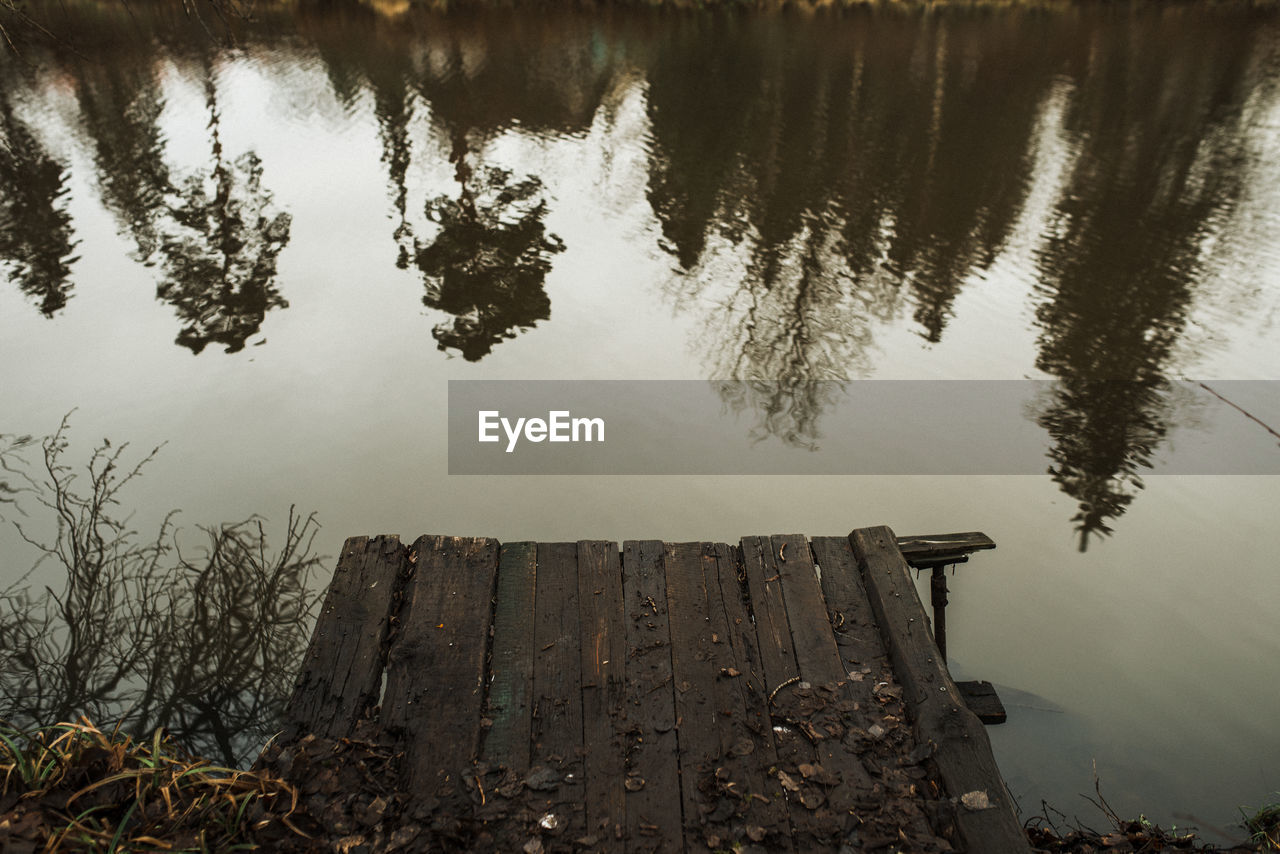 HIGH ANGLE VIEW OF WOODEN POSTS IN LAKE
