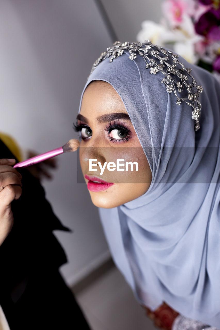 Cropped Hand Applying Make-Up On Woman Wearing Hijab