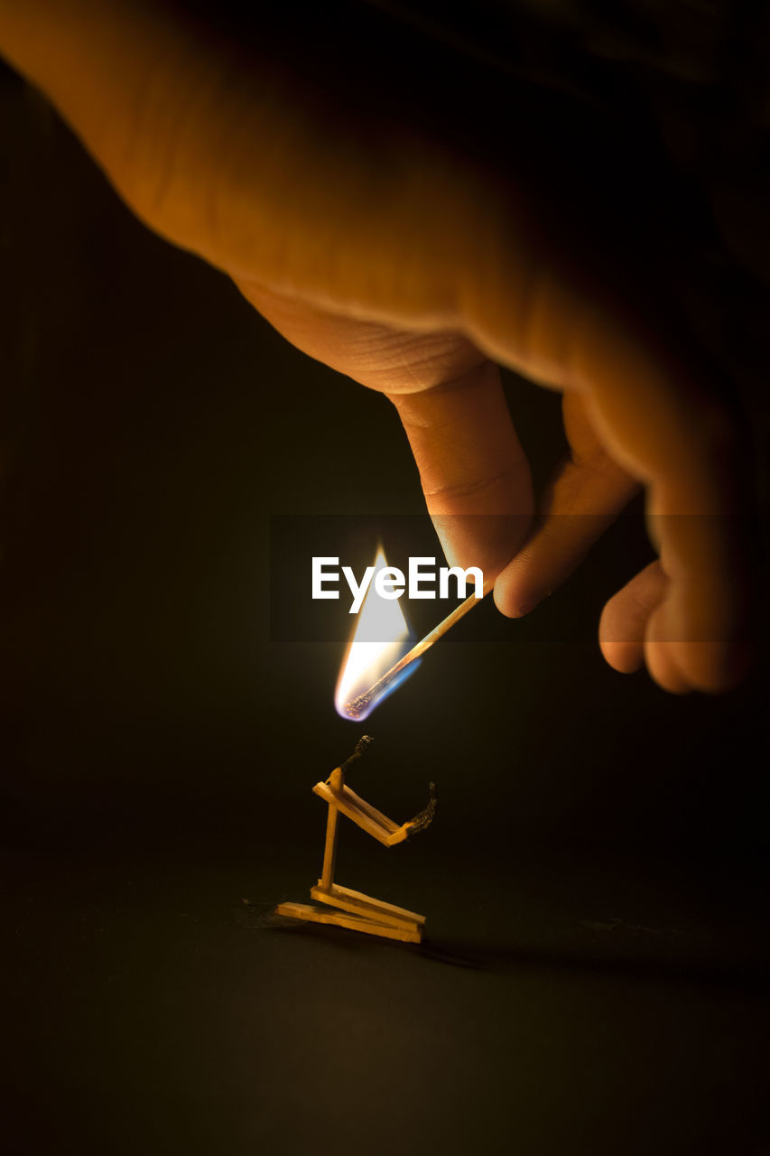 Person holding lit matchstick in dark