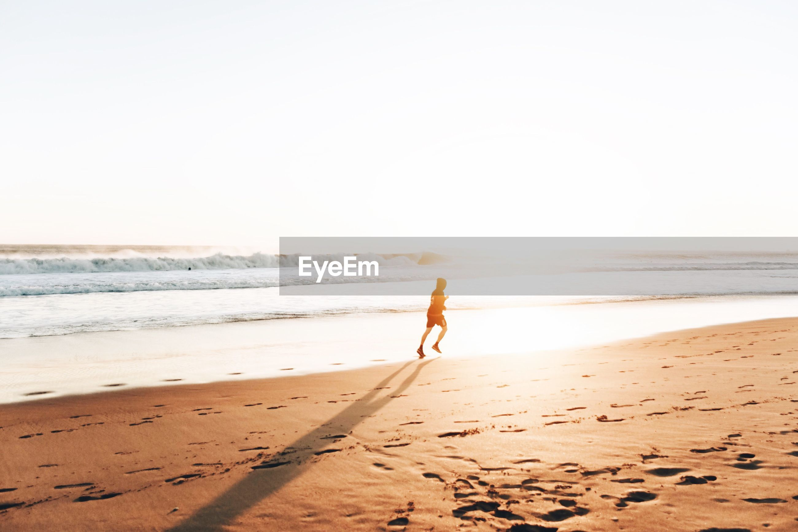 Man running on shore at beach against clear sky
