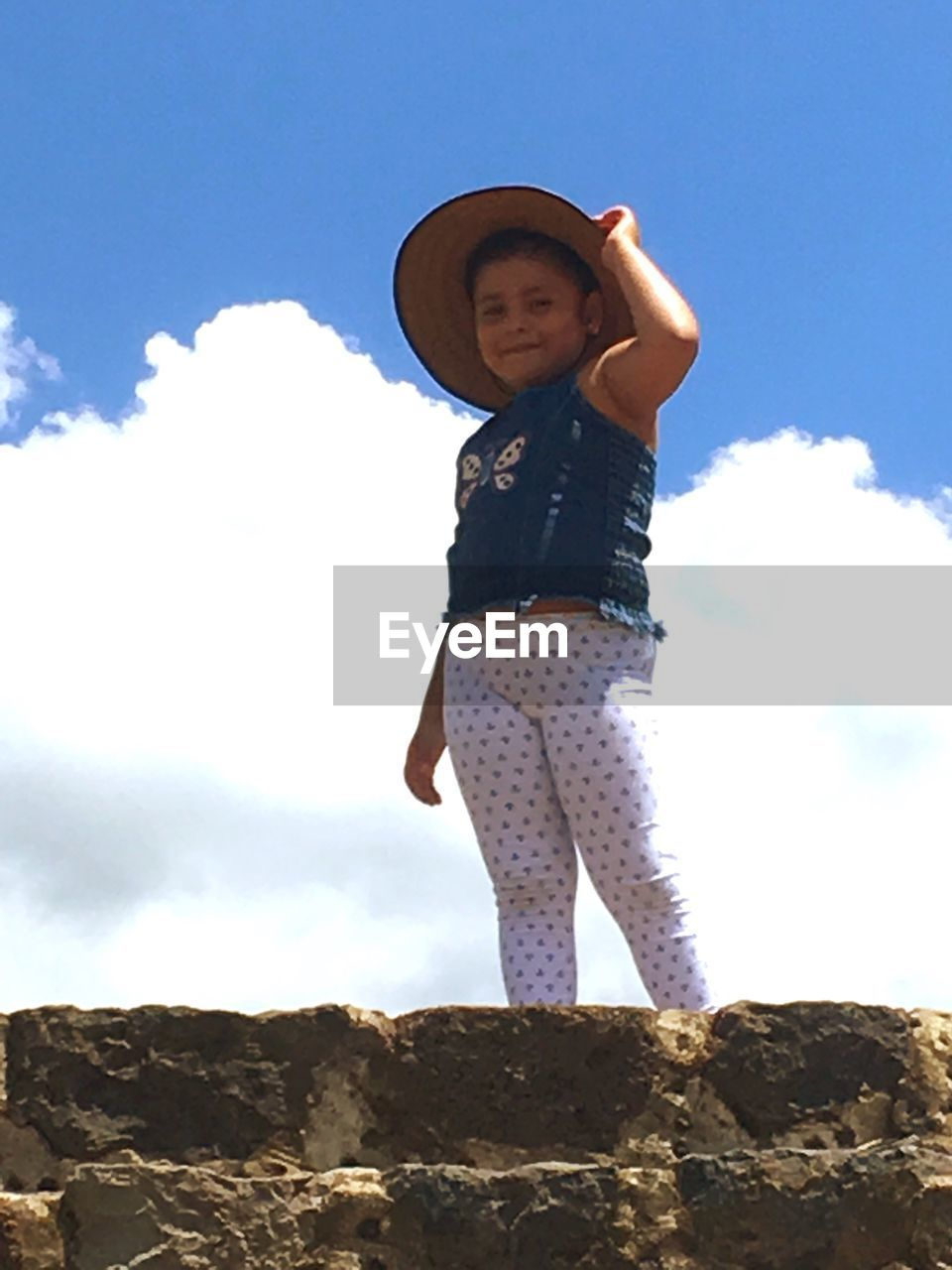 full length, real people, sky, standing, one person, hat, outdoors, casual clothing, day, childhood, leisure activity, low angle view, lifestyles, elementary age, cloud - sky, happiness, looking at camera, smiling, girls, young women, nature, young adult