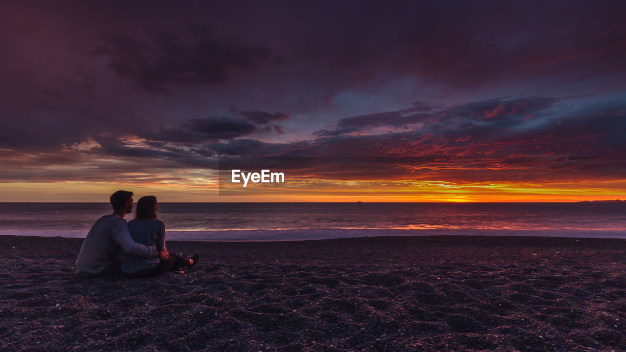sunset, sky, togetherness, two people, sitting, beach, cloud - sky, nature, sea, orange color, beauty in nature, scenics, tranquility, love, full length, outdoors, tranquil scene, men, vacations, sand, couple - relationship, women, horizon over water, real people, water, bonding, friendship, day, adult, people